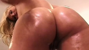 Oiled up blondie with a lot of junk in her fullness mounts a large shaft
